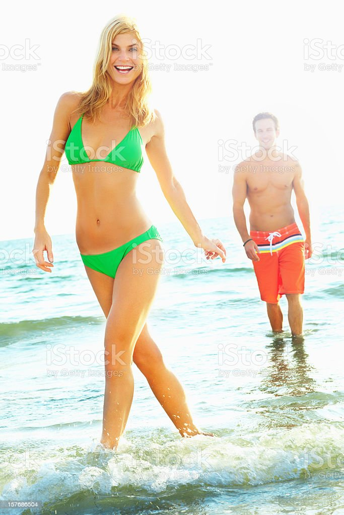 Joyful woman walking in water with a man at background royalty-free stock photo