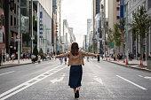 腕が付いている通りを歩いてうれしそうな女性を開く