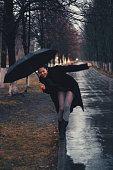 Joyful beautiful woman walks with an umbrella in the rain.