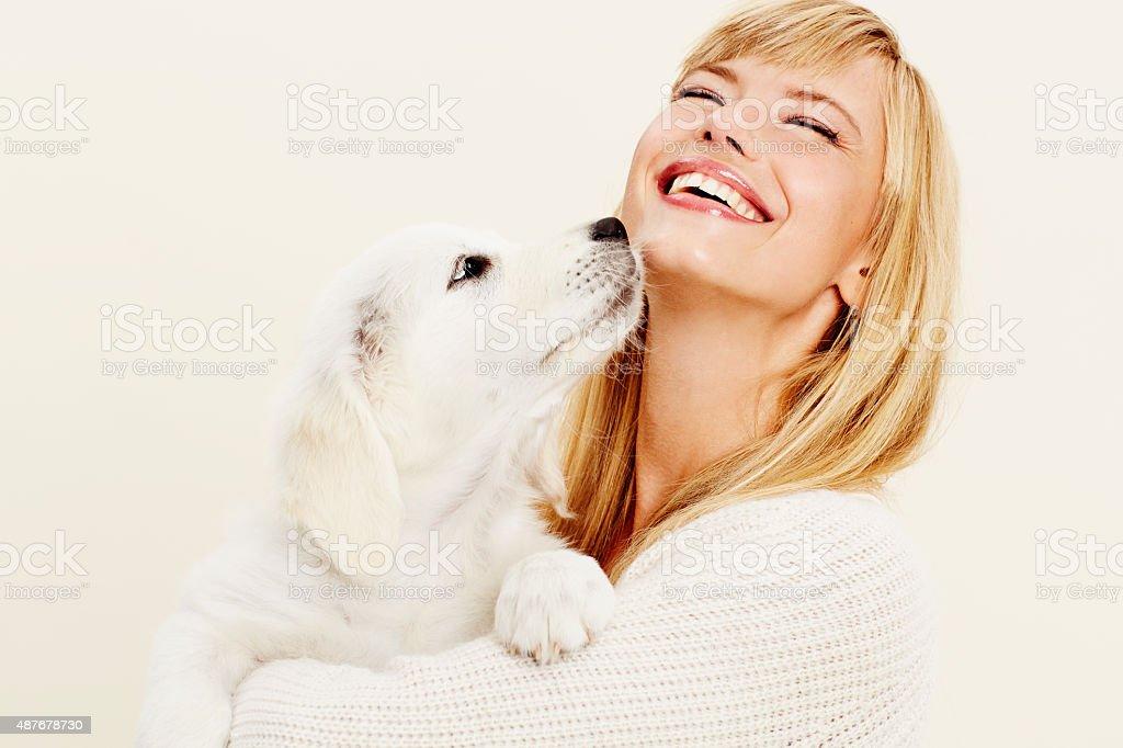 Joyful woman with pet puppy stock photo