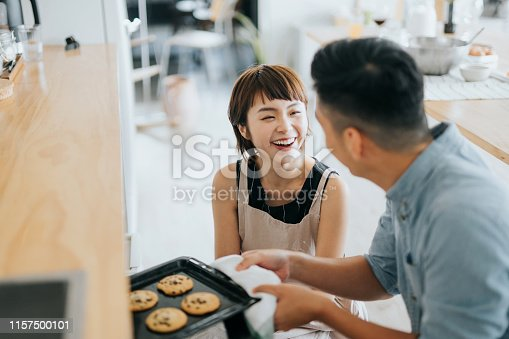 Joyful young Asian couple smiling at each other while taking out fresh home baked cookies from oven in a domestic kitchen