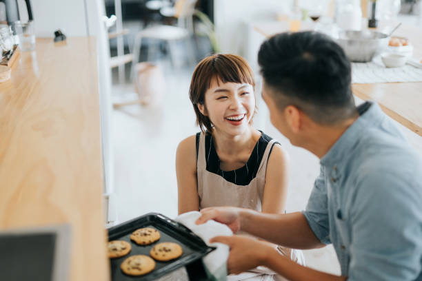 joyful young asian couple smiling at each other while taking out fresh home baked cookies from oven in a domestic kitchen - baking bread at home imagens e fotografias de stock