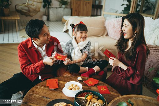 Joyful young Asian family celebrates Chinese New Year, parents giving red envelops (lai see) to their daughter and she receives them with both hands