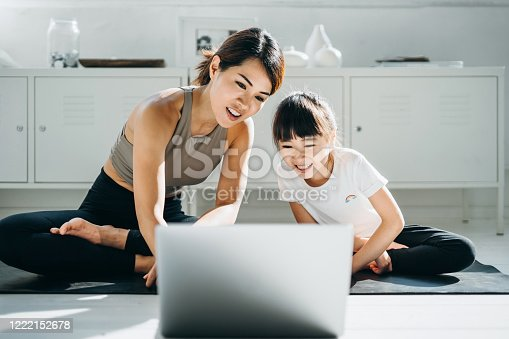 Joyful young Asian mother and little daughter doing online yoga class together with a laptop at home