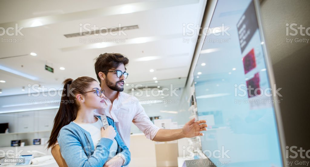 Joyful young attractive multiracial couple checking out plasma TVs in the electronic store. stock photo