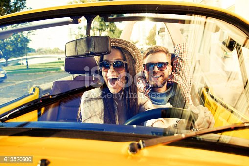 481388538 istock photo Joyful young couple smiling while riding in onvertible 613520600