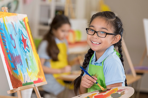 Beautiful Filipino elementary age art student smiles while working on a painting in art class.