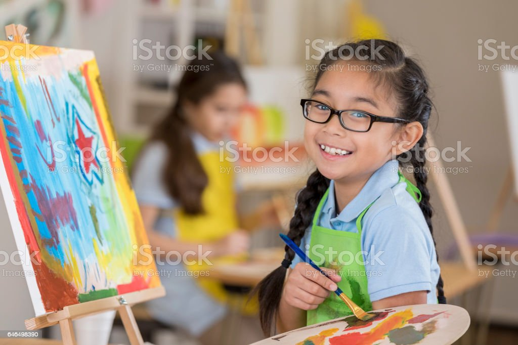 Joyful young female art student paints in a studio stock photo