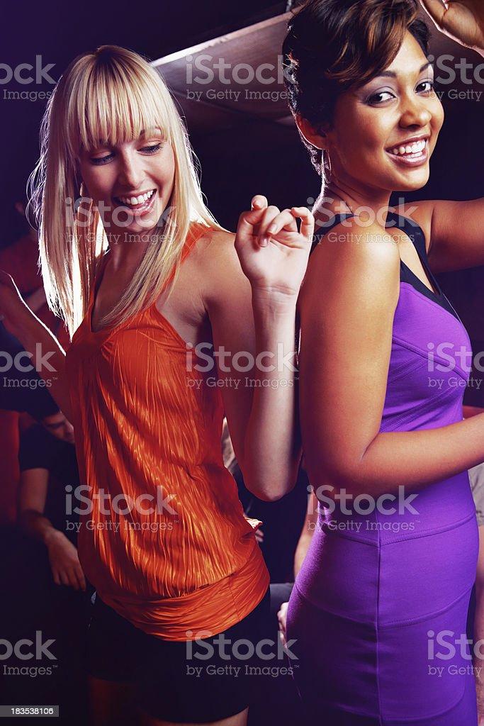 Joyful, young friends dancing and having fun at night club royalty-free stock photo