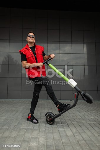 Joyful young hipster man with haircut in stylish denim red-black clothes in sunglasses poses with a modern electric scooter near a gray building. Cheerful cool guy riding a scooter around the city.