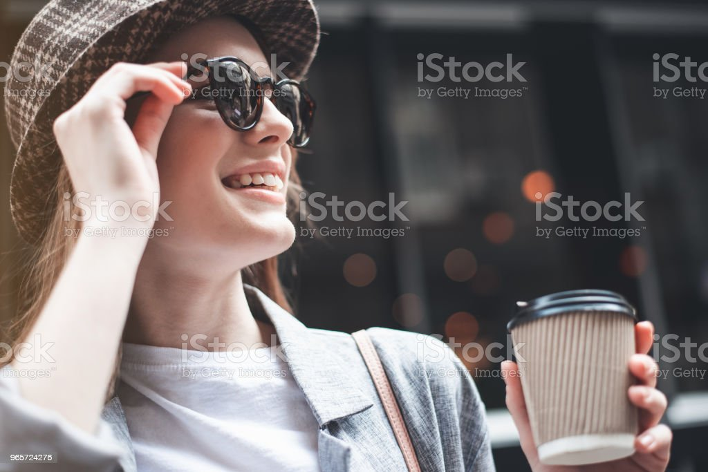 Joyful young lady in sunglasses with coffee outside - Royalty-free Adult Stock Photo