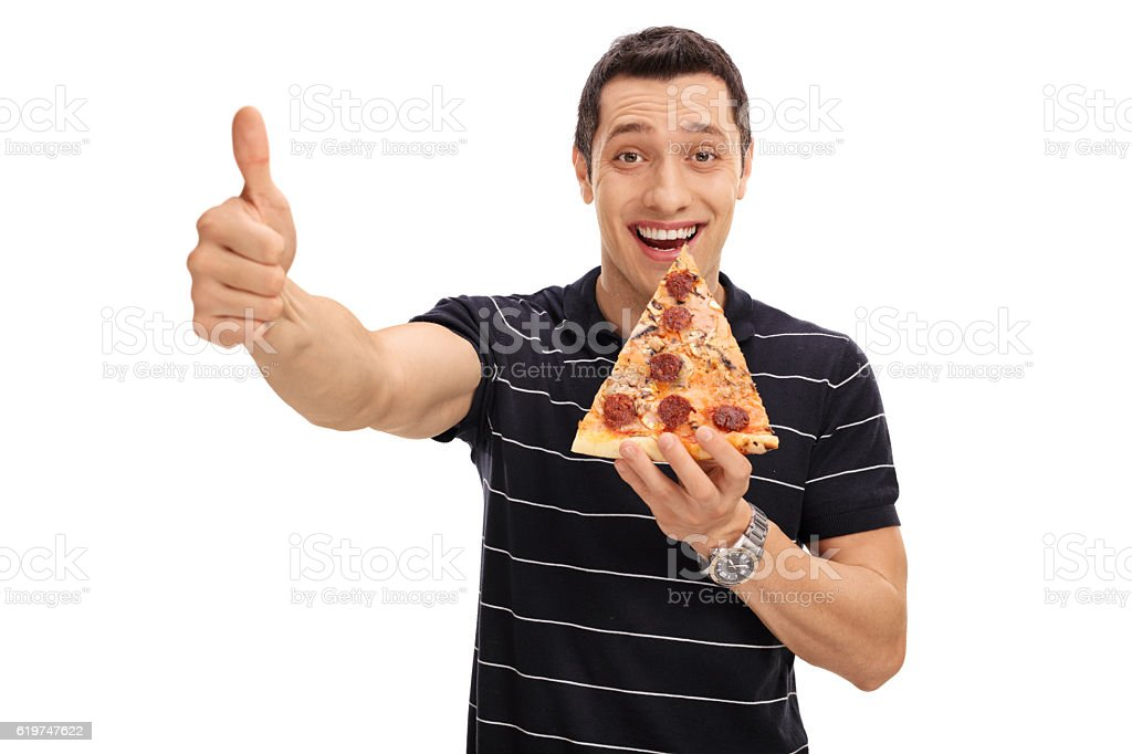 Joyful young man eating pizza slice and giving thumb up stock photo