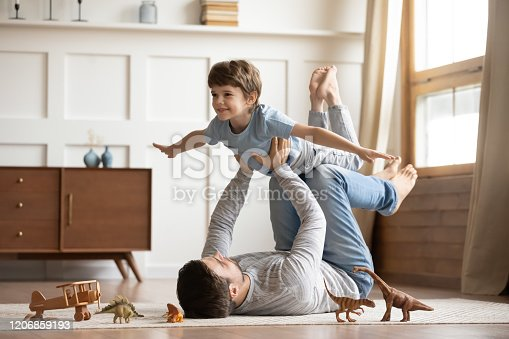 Joyful young man father lying on carpet floor, lifting excited happy little child son at home. Full length carefree two generations family having fun, practicing acroyoga in pair in living room.