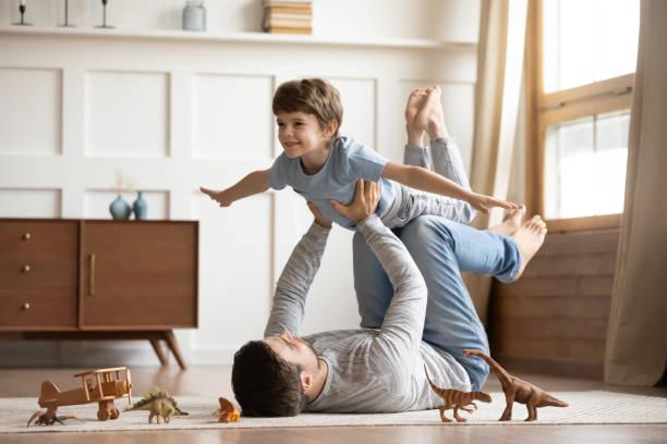 gioioso giovane padre sollevando eccitato figlio piccolo felice. - family foto e immagini stock