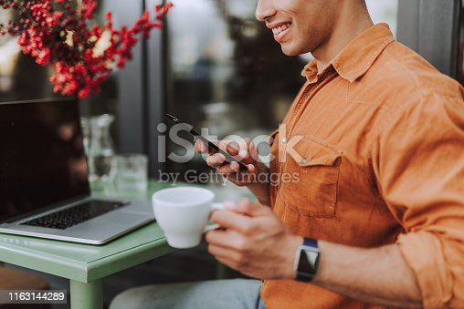 Close up of smiling afro american guy in orange shirt holding cup of coffee and checking messages on smartphone. He sitting at the table with modern laptop