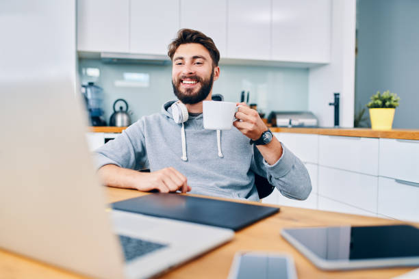 Joyful young web developer drinking coffee while taking break from work in home office stock photo