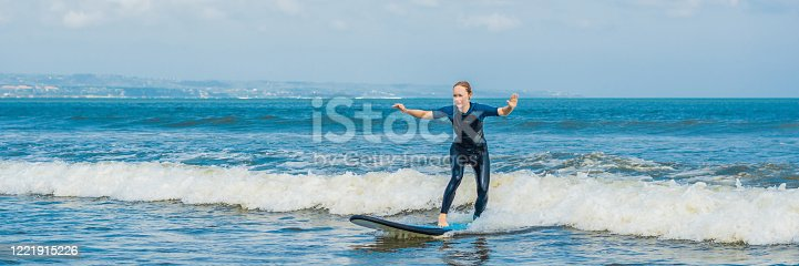 583830686 istock photo Joyful young woman beginner surfer with blue surf has fun on small sea waves. Active family lifestyle, people outdoor water sport lesson and swimming activity on surf camp summer vacation BANNER, LONG FORMAT 1221915226