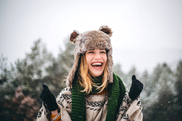 Joyful young woman enjoys cold winter day in mountains stock photo