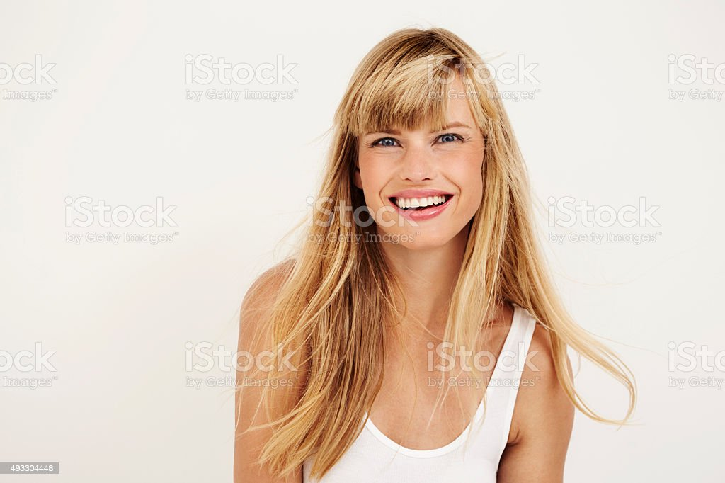 Joyful young woman smiling at camera in studio stock photo