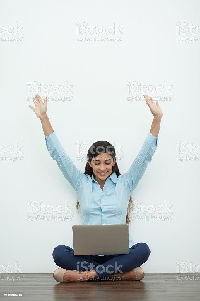 Joyful Young Woman Working on Laptop on Floor stock photo