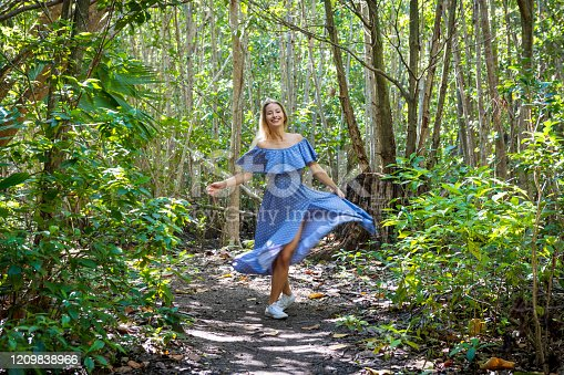 A young woman in a beautiful blue dress spins and dances on a wilderness trail in Fort Lauderdale, Florida.