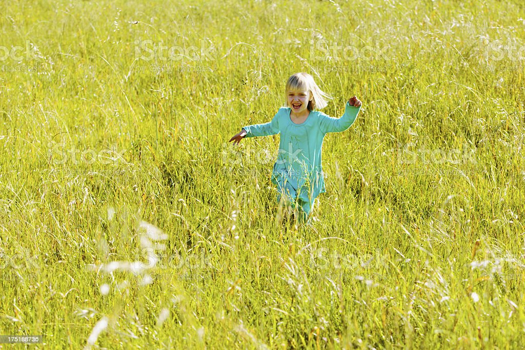 Joyfully excited little girl runs through grassy field stock photo
