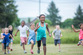 A multi-ethnic group of elementary age children are playing tag together at recess. They are running and chasing each other through a grassy field.