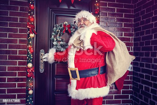 istock Joyous coming Santa Claus in home for Christmas 884447966