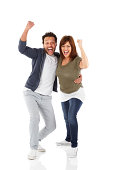 Full length portrait of excited mature couple standing together with their hands raised and screaming over white background