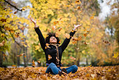 istock Joyous teen playing with dry maple leaves 1016602340