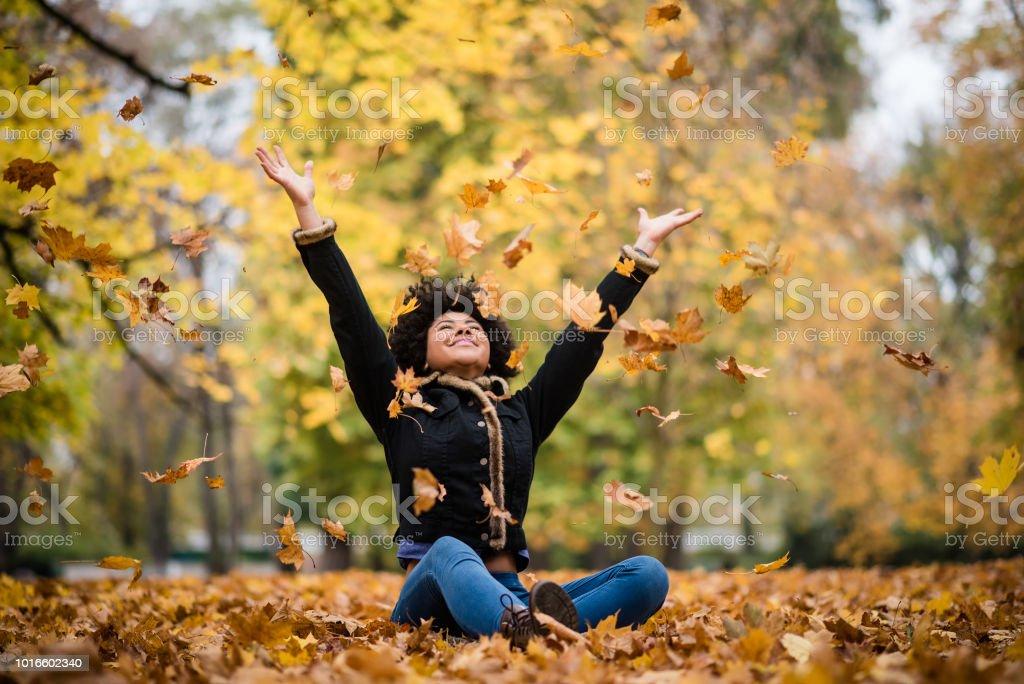 Freudige Teen spielt mit trockenen Ahornblätter – Foto