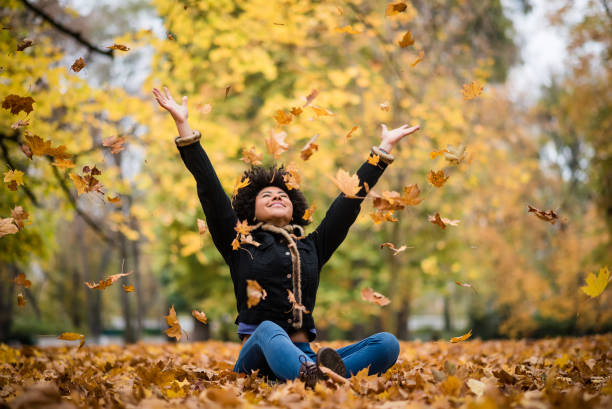 Joyous teen playing with dry maple leaves Happy woman in autumn park drop up leaves autumn leaf color stock pictures, royalty-free photos & images