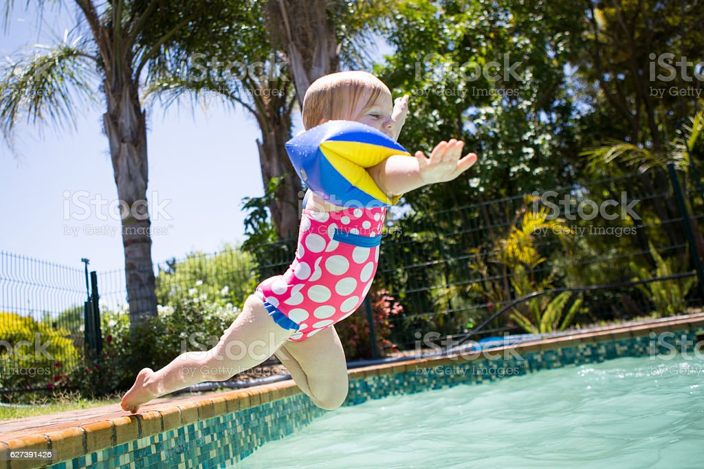 Jubilant baby girl jumps into the swimming pool stock photo