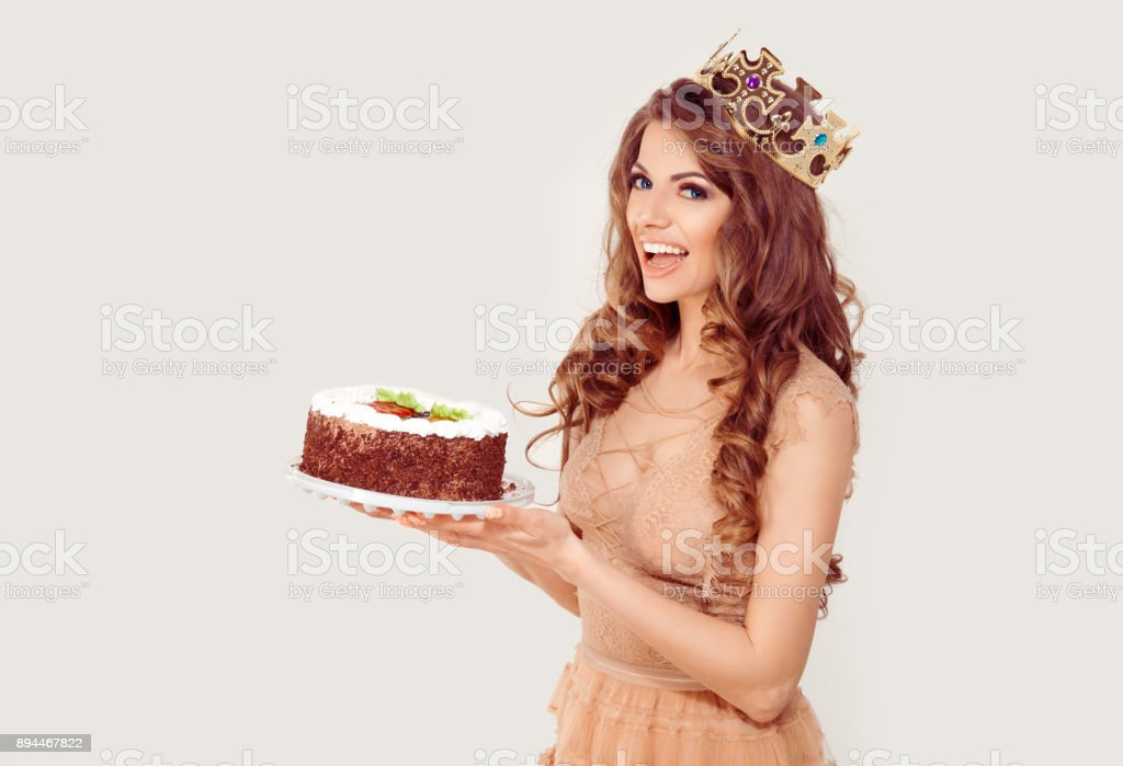 Jubilee. Excited happy middle age beautiful woman holds her birthday cake wearing party golden crown white background. Girl with full makeup curly brown long hair blue eyes beige skin tone lace dress stock photo