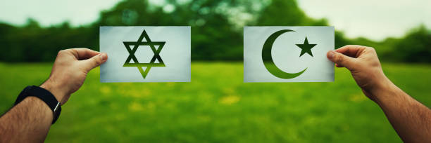 Judaism vs Islam belief Religion conflicts as global issue concept. Two hands holding different faith symbols, Judaism vs Islam belief over green field nature background. Relations between different people doctrines and cult religious symbol stock pictures, royalty-free photos & images