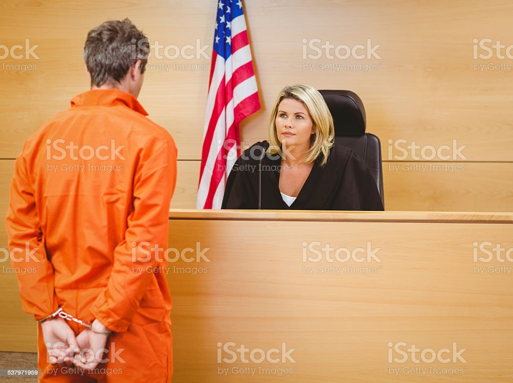 Judge and criminal speaking in front of the american flag stock photo