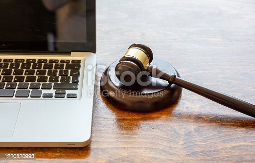 Auction law gavel and a computer laptop, wooden office desk background, closeup view, Online auction, cyber crime  concept