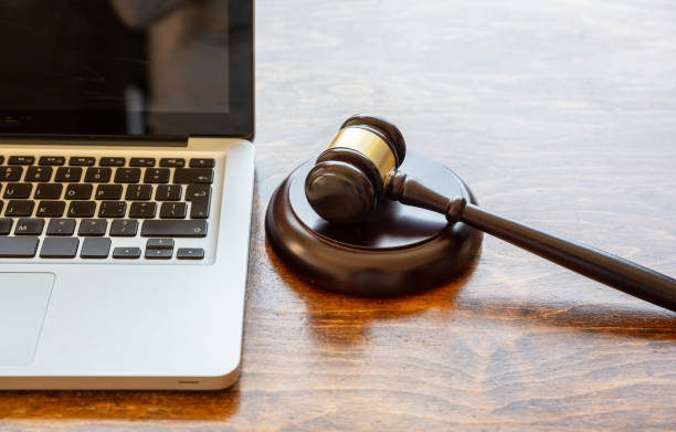 Judge gavel and a laptop, wooden background. Online auction concept Auction law gavel and a computer laptop, wooden office desk background, closeup view, Online auction, cyber crime  concept courtroom stock pictures, royalty-free photos & images