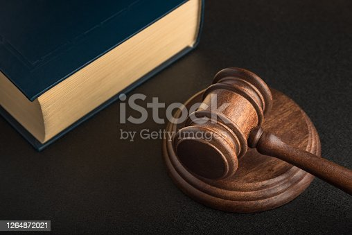 Judge gavel and book. Black background. Wooden hammer. Justice and law.