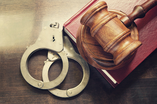 istock Judge gavel and handcuffs with red legal book 1179159563