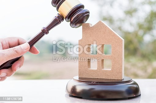 istock Judge gavel and house model property auction for real estate law concept. Lawyer hand holding gavel wooden knocking home ownership for buying selling or foreclosure on nature background. 1138129738