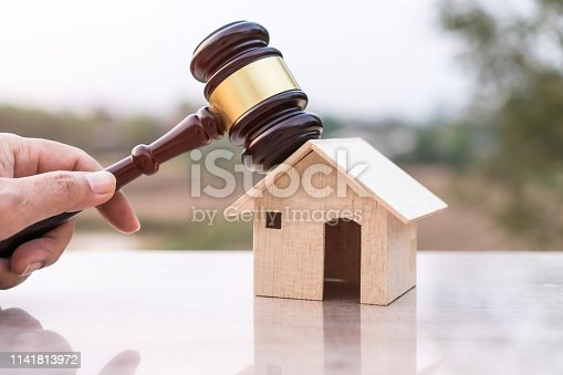 istock Judge gavel and house model property auction for real estate law concept. Lawyer hand holding gavel wooden knocking home ownership for buying selling or foreclosure on nature background. 1141813972