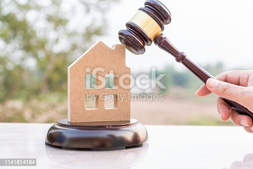 istock Judge gavel and house model property auction for real estate law concept. Lawyer hand holding gavel wooden knocking home ownership for buying selling or foreclosure on nature background. 1141814184