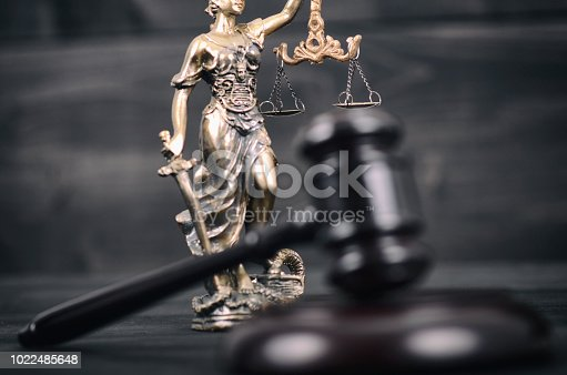 istock Judge Gavel and Lady Justice on a black wooden background. 1022485648