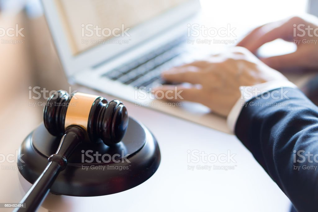 Judge gavel and lawyer working on a laptop stock photo