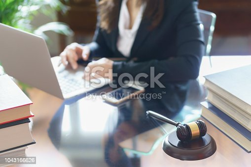 663458084 istock photo Judge gavel and lawyer working on a laptop. Selective focus 1043166626