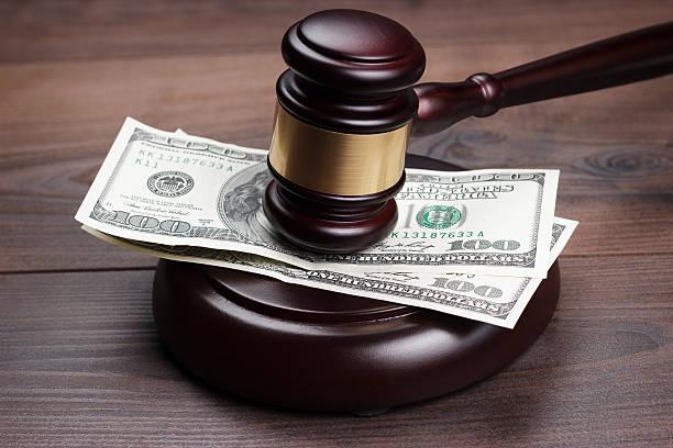 juez martillo y dinero en marrón mesa de madera - indemnización compensación fotografías e imágenes de stock