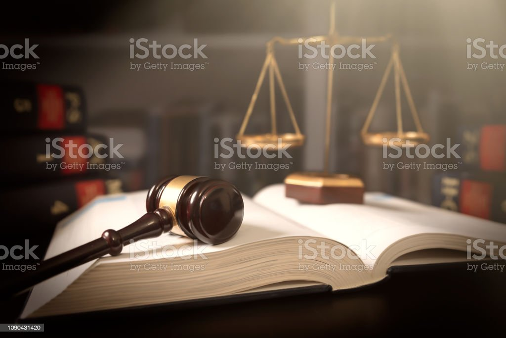 Judge gavel and scale in court. Legal concept Judge gavel and scale in court. Library with lot of books in background Auction Stock Photo