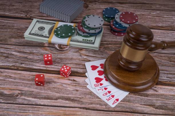 judge gavel and set of playing cards with dices, money and chips stock photo