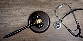 Judge gavel beside medical stethoscope on wooden table. Panoramic image.
